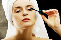 Woman makes light day makeup in bathroom. Royalty Free Stock Image