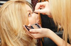Woman makes make-up. To another woman Stock Photos