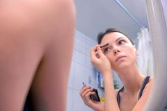 Beautiful brunette woman paints the eyebrows in bathroom in front of the mirror. Woman makes make-up in bathroom in front of the mirror stock photos