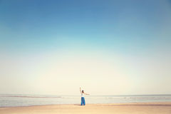 Woman makes meditation exercises facing the sea Royalty Free Stock Photography