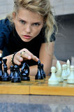 Woman makes a move chess elephant. Royalty Free Stock Images