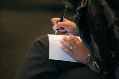Woman makes a note in notebook closeup Stock Photography