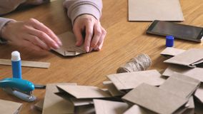 Woman makes a paper bags from kraft paper for advent calendar. Hands close-up. Glue the paper. stock video