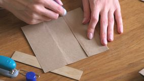 Woman makes a paper bags from kraft paper. Hands close-up. Glue the paper. stock footage