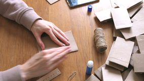 Woman makes a paper bags from kraft paper for advent calendar. Hands close-up. Bends the ruler. stock video
