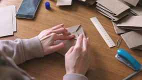 Woman makes a paper bags from kraft paper. Hands close-up. stock video