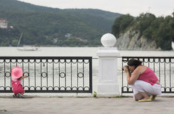 Woman makes photo of a daughter outdoors in sommer, near nice la. Ke and mountains royalty free stock photo