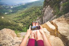 Woman makes photo of landscape. Woman makes photo of her boots and landscape background sitting at the edge of a rock near stream. View on behalf of royalty free stock photo