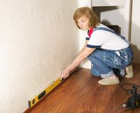Woman makes repairs in the apartment Royalty Free Stock Photo