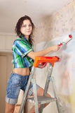 Woman makes repairs in  apartment Stock Photos
