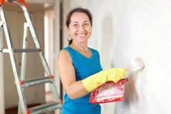 Woman makes repairs in  apartment Royalty Free Stock Image