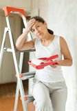 Woman makes repairs at home. Weariness mature woman makes repairs at home Royalty Free Stock Photography