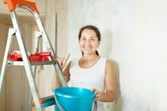 Woman makes repairs at home Stock Photo
