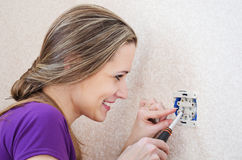 Woman makes repairs to electrical socket Royalty Free Stock Photo