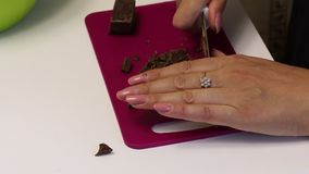 Woman makes shavings of dark chocolate. With a knife, on a cutting board. To make a dessert.  stock video