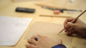 Woman makes sketch on rude brown paper with slate pencil in art studio. stock footage