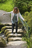 A Woman Makes a Tentative Creek Crossing. A Woman Holds a Railing as She Tentatively Crosses a Creek on Stepping Stones Royalty Free Stock Photography