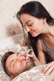 Woman makes up the man`s lips with lipstick Stock Photo