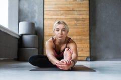 Woman makes yoga pose in class, sit forward bend asana Stock Photos