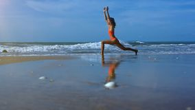 Woman Makes Yoga Warrior Pose on Beach near Foamy Waves. Side view young athletic woman in orange swimsuit makes yoga warrior pose on beach against ocean stock video footage