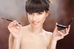 Woman and makeup. Young pretty girl holding powder brush and makeup set stock images