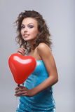 Woman with makeup. Close-up of a young, beautiful, brown-haired woman with red balloon Stock Images