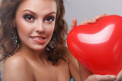 Woman with makeup. Close-up of a young, beautiful, brown-haired woman with red balloon Stock Photography