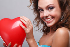 Woman with makeup. Close-up of a young, beautiful, brown-haired woman with red balloon Stock Image