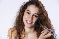 Woman makeup. Happy beautiful woman applying some powder brush in her face Royalty Free Stock Photos