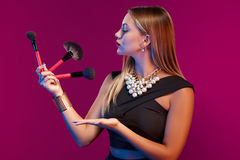 Woman makeup artist standing with brushes Stock Photography