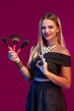 Woman makeup artist standing with brushes Stock Photo