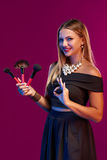 Woman makeup artist standing with brushes Stock Photos
