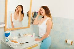 Woman without makeup in bathroom. Happy young girl woman without makeup in bathroom standing in front of mirror smiling. Natural beauty. Purity stock photography