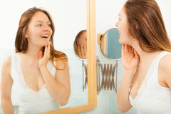 Woman without makeup in bathroom. Happy young girl woman without makeup in bathroom standing in front of mirror smiling. Natural beauty. Purity stock photos