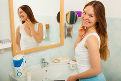 Woman without makeup in bathroom. Happy young girl woman without makeup in bathroom standing in front of mirror smiling. Natural beauty. Purity royalty free stock photos