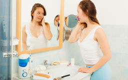 Woman without makeup in bathroom. Young girl woman without makeup in bathroom looking in mirror. Natural beauty. Purity royalty free stock photography