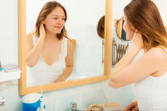 Woman without makeup in bathroom. Young girl woman without makeup in bathroom looking in mirror. Natural beauty. Purity royalty free stock photo
