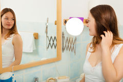 Woman without makeup in bathroom. Young girl woman without makeup in bathroom looking in mirror. Natural beauty. Purity stock images