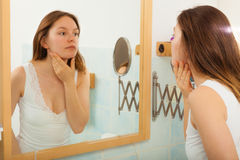 Woman without makeup in bathroom. Young girl woman without makeup in bathroom looking in mirror. Natural beauty. Purity stock image