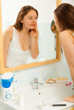 Woman without makeup in bathroom. Young girl woman without makeup in bathroom looking in mirror. Natural beauty. Purity stock photo