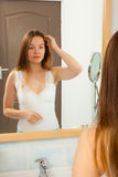 Woman without makeup in bathroom. Young girl woman without makeup in bathroom looking in mirror. Natural beauty. Purity royalty free stock image