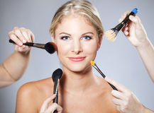 Woman makeup brush. Beautiful woman surrounded by makeup brushes Royalty Free Stock Photography