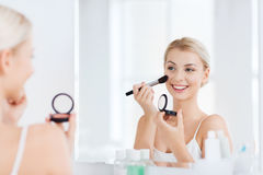 Woman with makeup brush and blush at bathroom Royalty Free Stock Photos