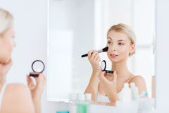 Woman with makeup brush and blush at bathroom Royalty Free Stock Photo