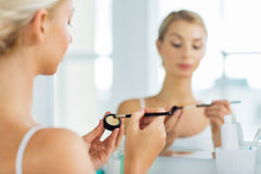 Woman with makeup brush and eyeshade at bathroom Stock Photography