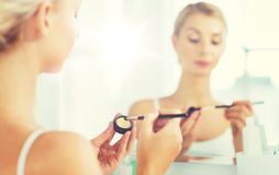 Woman with makeup brush and eyeshade at bathroom Royalty Free Stock Images