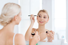 Woman with makeup brush and eyeshade at bathroom Stock Images