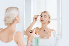 Woman with makeup brush and eyeshade at bathroom Stock Photos