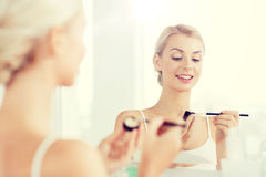 Woman with makeup brush and eyeshade at bathroom Royalty Free Stock Photo