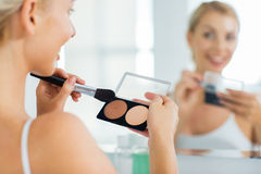 Woman with makeup brush and foundation at bathroom Royalty Free Stock Image